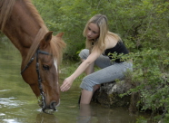 Girl with horse at peaceful creek