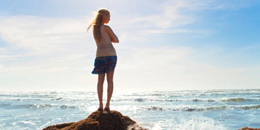 Girl Facing Sea on Rocks