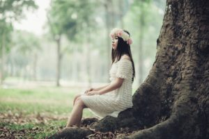 Woman sitting at tree base
