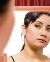 Woman judging herself in the mirror