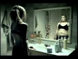 Girl looking into mirror concerned with Body image and adolescent girls