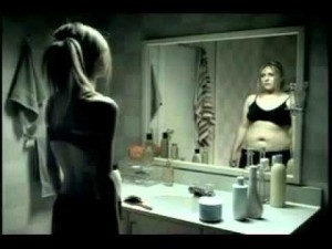 Woman looking at her body in the mirror and dealing with body image concerns
