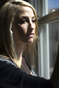 Blond girl looking out a window struggling with Suicide