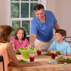 Family sitting down for dinner with new meal plan