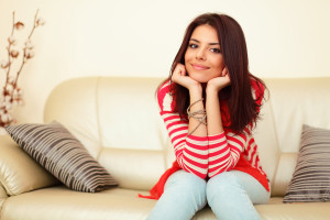 Smiling teen girl in colorful cloths sitting on the sofa and relaxing
