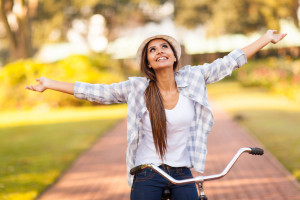 young woman enjoying riding bike outdoors