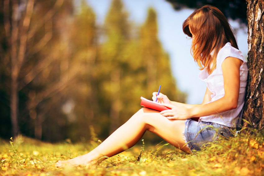 College girl leaning on tree reading a book