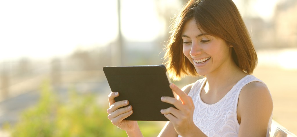 Happy woman using a tablet outdoors