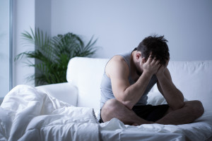 Young man thinking about binge eating disorder in males