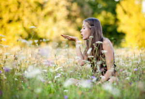 girl blowing dandelions in field