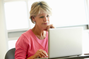 Mature Woman Looking At Eating Disorder Volunteering Options On Her Computer