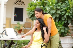 Loving mother and daughter sharing computer in outdoors