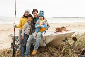 Family Group Sitting On Boat With Fishing Rod On Winter Beach