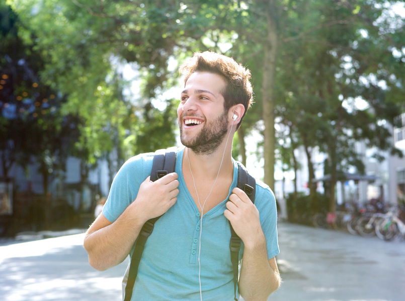 Happy young man traveling with backpack