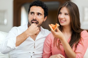 Couple eating pizza and watching TV