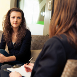 Woman discussing in-home eating disorder challenges with therapist.