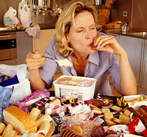 Lady eating and contemplating Binge Eating Disorder vs Basic Overeating
