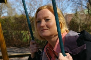 middle-aged woman sitting on swing