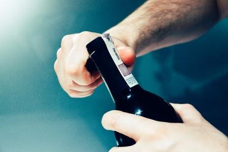 Man suffering from drunkorexia opening bottle of wine
