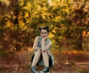 Girl sitting under pine tree