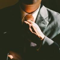 Man adjusting his tie and increasing his Self-worth