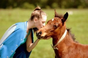 Girl kissing horse during equine therapy