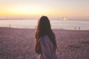 Woman on beach thinking about Eating disorder treatment in the summer