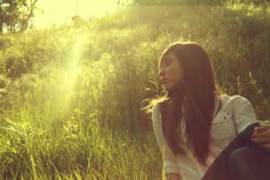 Woman in the grass experiencing Mindfulness
