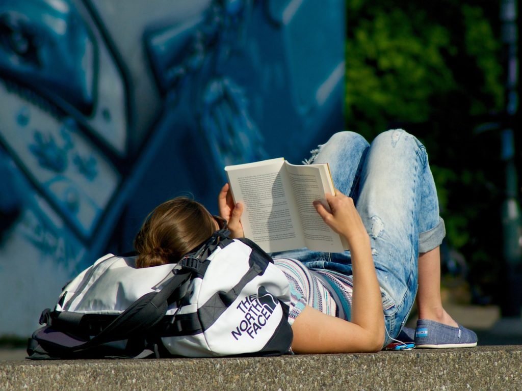 College student reading a book on Poly-substance Abuse