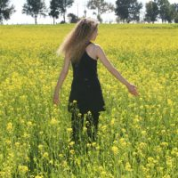 Woman recovering from eating disorder in a field