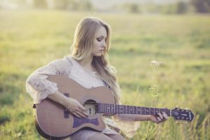 Young woman playing the guitar happy about transitional living for her eating disorder