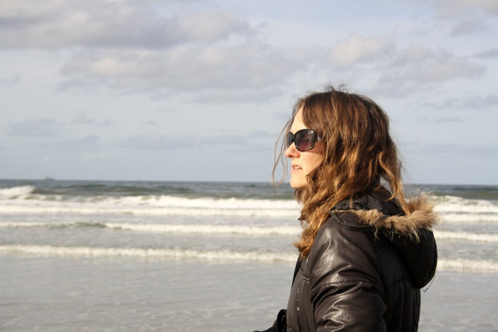 Woman walking on the beach outside her treatment program