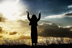 Woman raising hands in faith