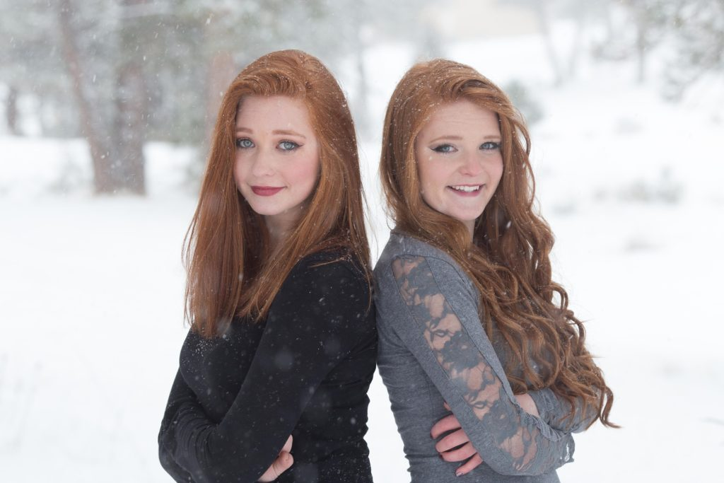 Sisters standing back-to-back in the snow