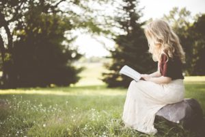 Woman sitting in grass reading about Binge Eating Disorder