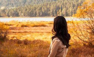 Woman looking at a lake thinking about binge eating