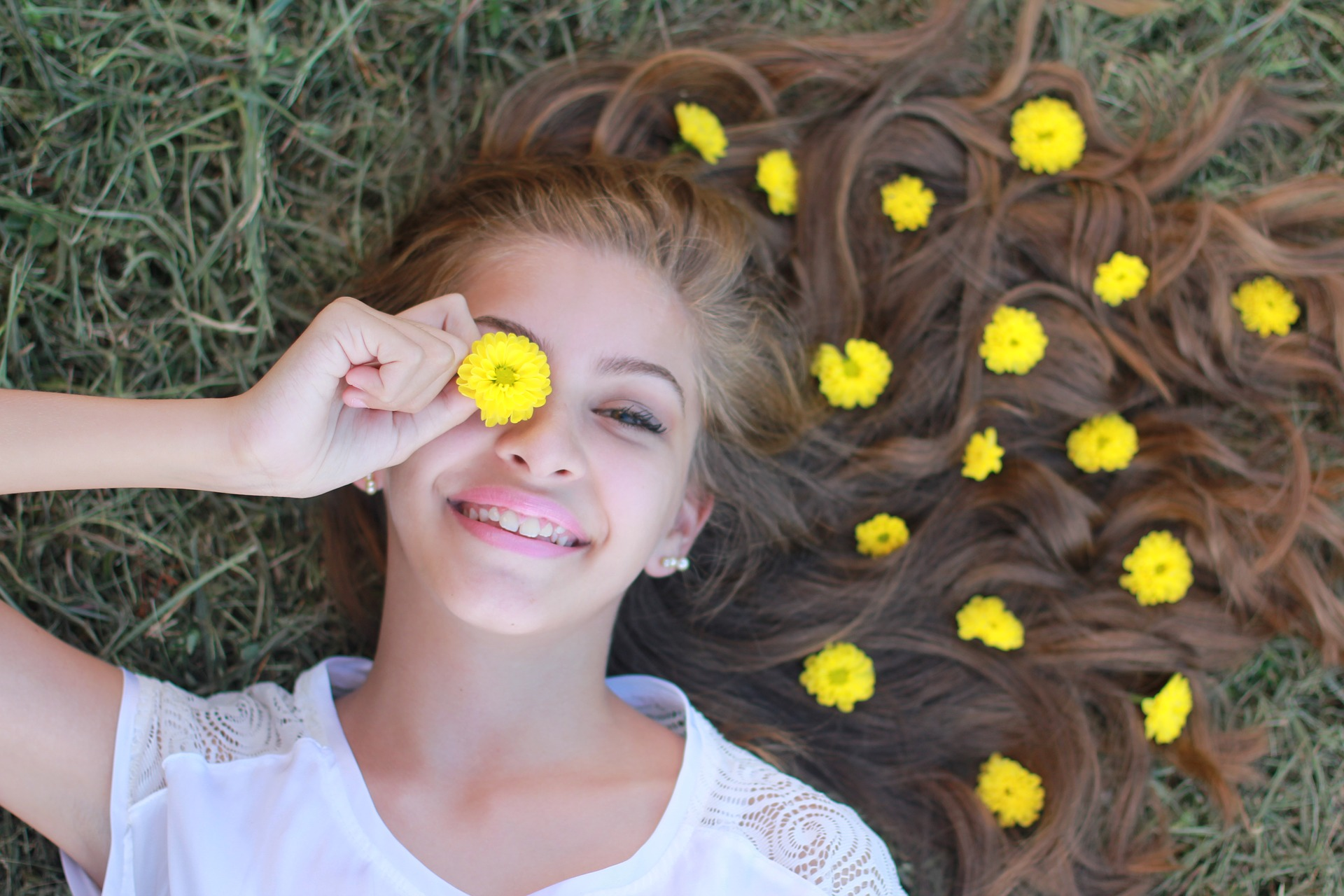 Girl laying grass with flowers