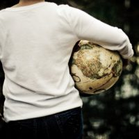 Woman holding world globe while in Eating Disorder Recovery