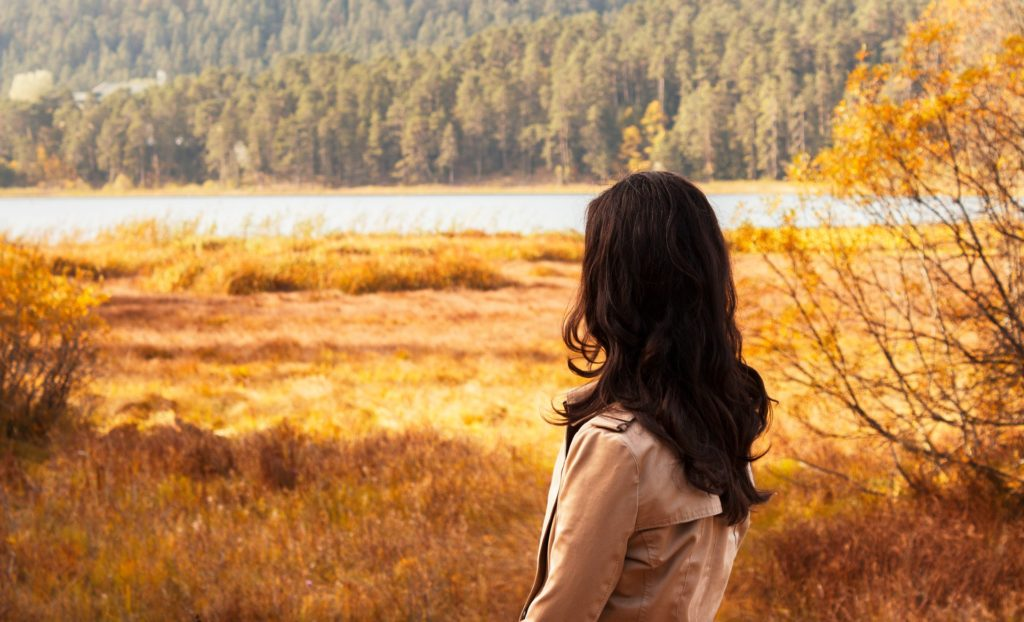 Woman struggling with bulimia looking at lake