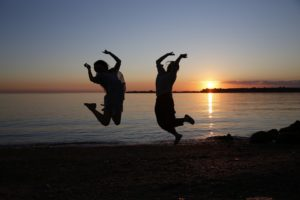 Girls jumping on beach, celebrating scholarship