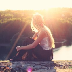 Woman sitting on a cliff thinking about BED recovery