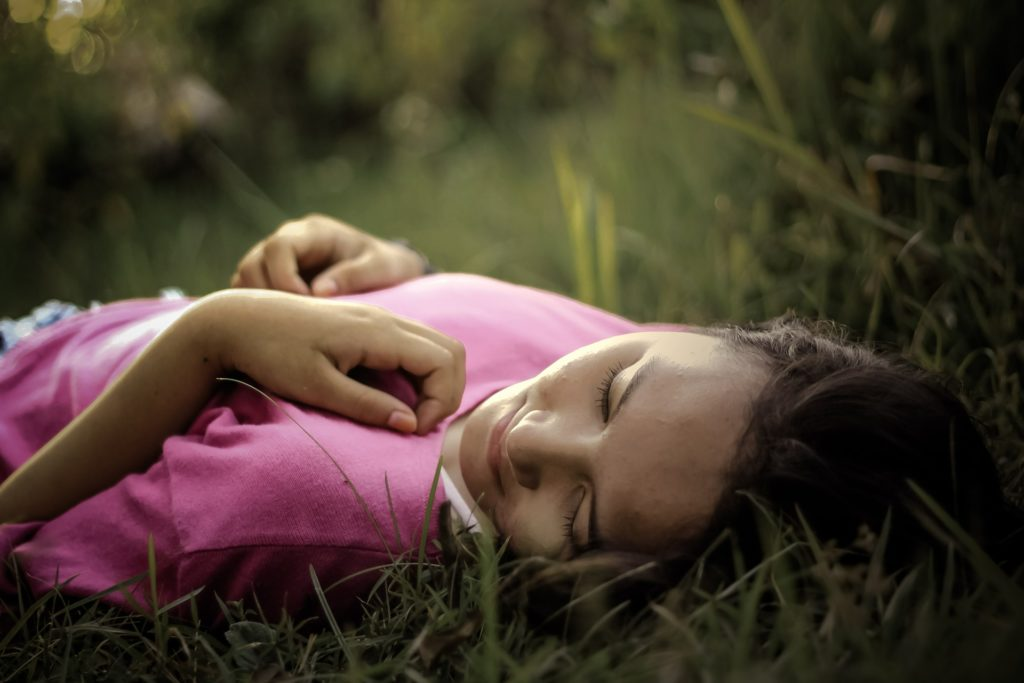 Woman laying in grass thinking of treatment