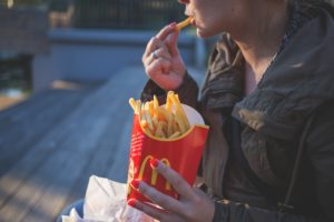 Woman eating fries struggling with Binge Eating Disorder