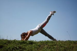 Woman doing yoga in the grass