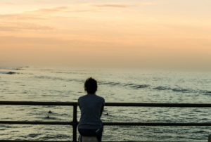 Woman watching the sunset as she thinks about her eating disorder and addiction.