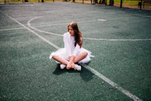 Young woman with ballet attire sitting on the tennis court