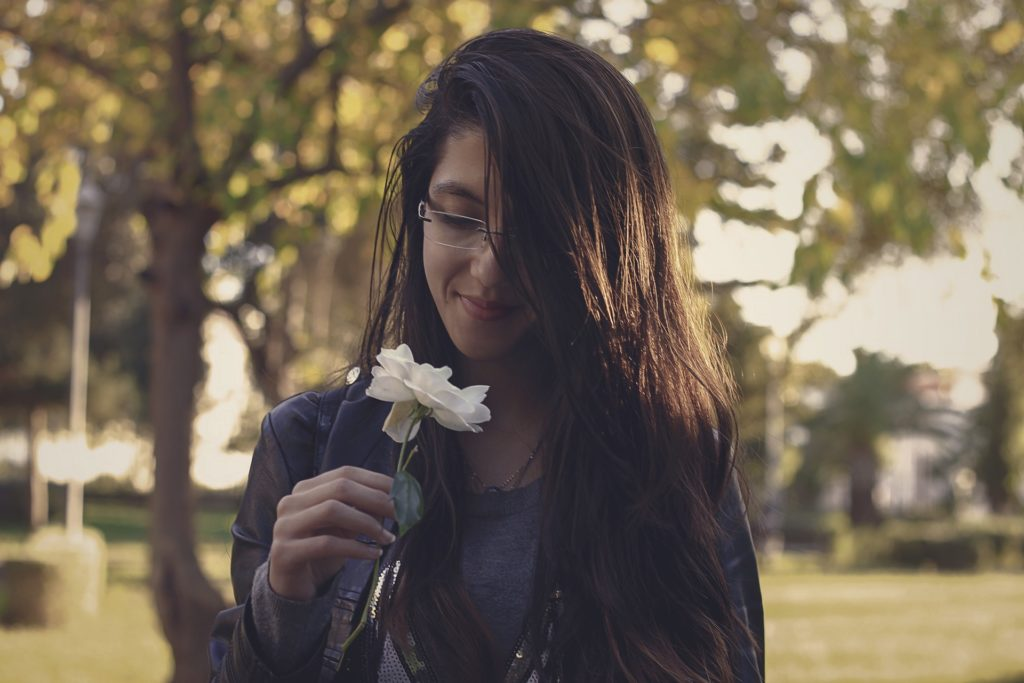 Woman smelling a flower and using Mindfulness in Eating Disorder Recovery