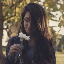 Woman smelling a flower considering treatment programs