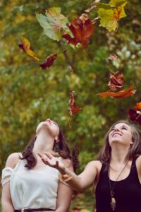 Girls looking at the fall leaves