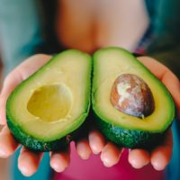 Woman who eats vegan holding an avacado